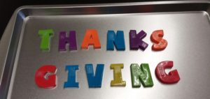"Magnetic Letters on a cookie sheet spelling the word ""Thanksgiving""."
