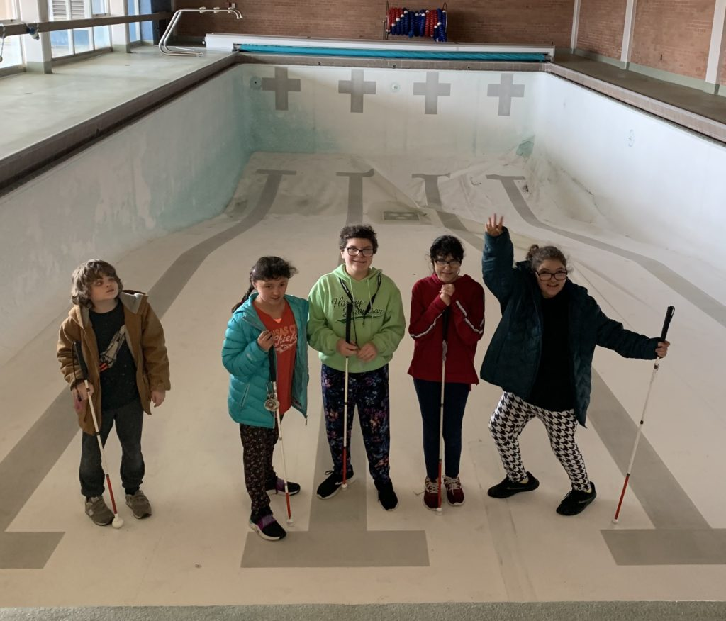 Several students standing on the bottom of an empty pool.