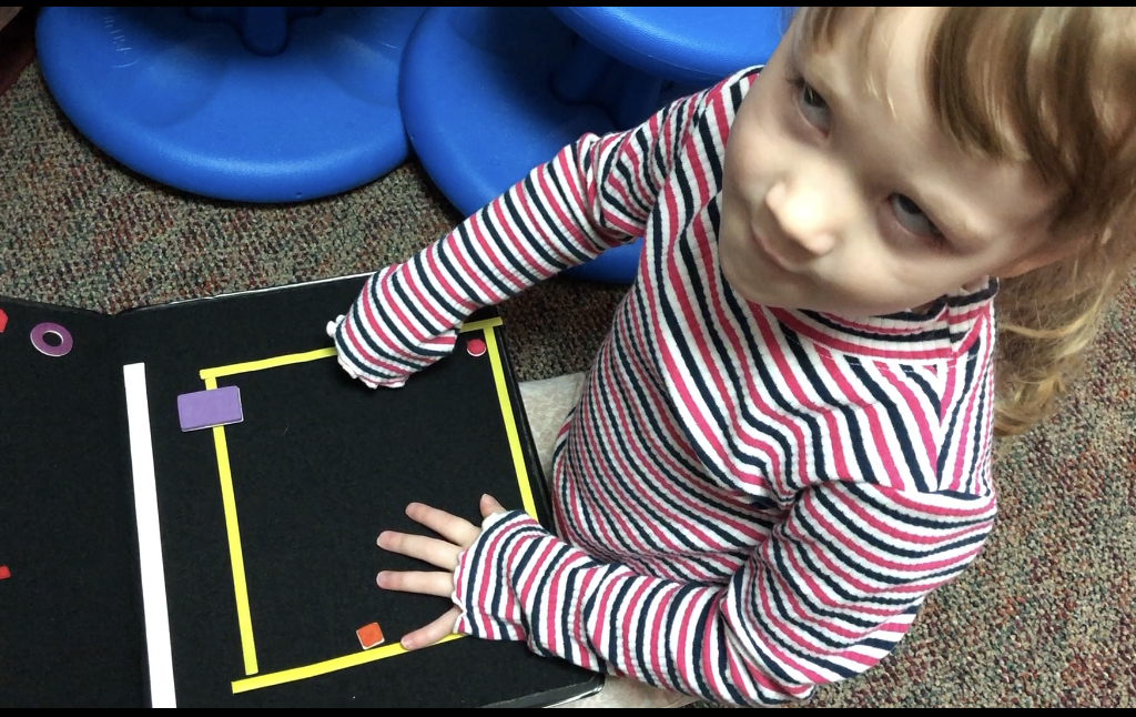 Student looking at camera while using hands to explore a velcro board with strips to create a square.