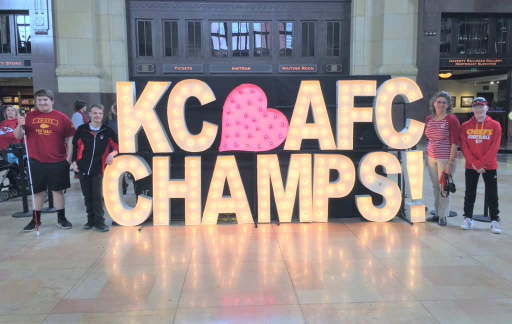 Student standing to the right and left of the KC heart AFC CHAMPS! Sign.