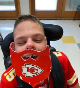 Student Holding Up A KC Chiefs Mask And Wearing A KC Chiefs Shirt.