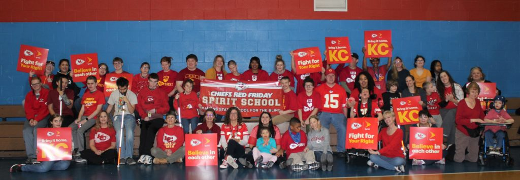 "Chiefs Red Friday Spirit - Large group of Students and staff in KSSB wearing red Chiefs shirts and holding signs. ""Fight for your Right"", ""Believe in each other"", and ""Bring it home KC""."
