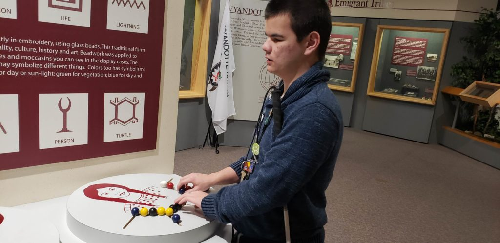 Student with hands on an exhibit of blue, yellow, white, and red beads.