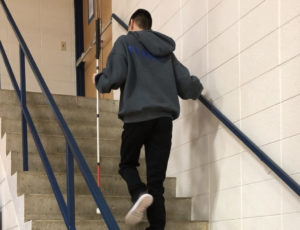 Student climbing stairs with his cane.