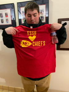 A adult holding up a red t-shirt with KSSB, heart, KC Chiefs printed on the front.