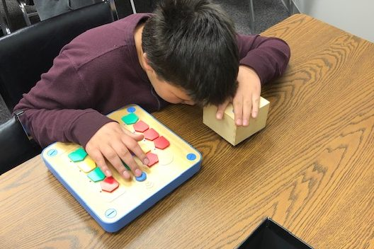 Student tactually exploring a cubetto coding tool. A square shape with pegs placed in a sequence.
