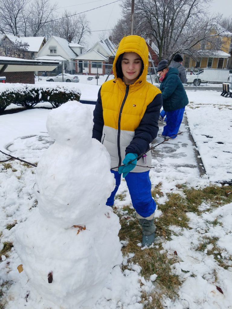 Student in a warm yellow, white and blue winter coat, holding the stick arm of his snowman.