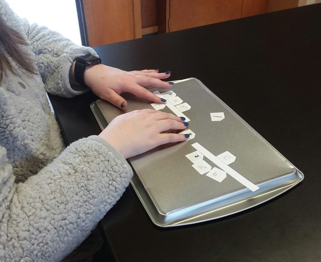 Students with hands on Nemeth Code magnetic squares set on a cookie sheet.