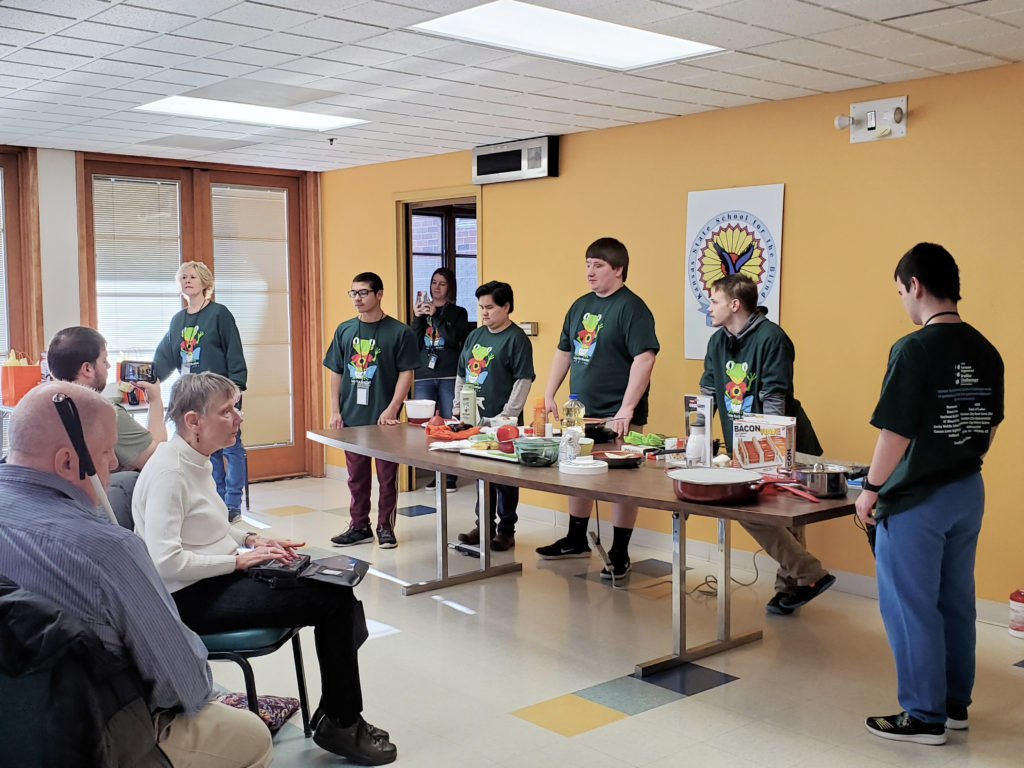 Several Students standing in front of a long table containing a variety of cooking and labeling tools.