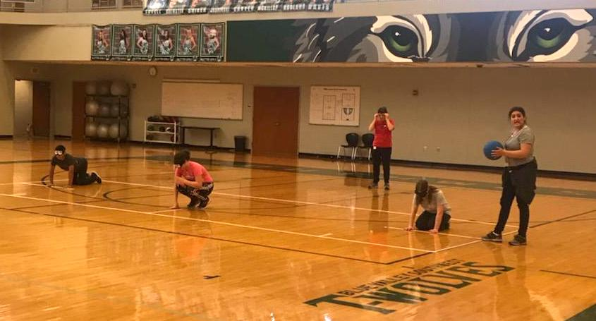 Five students on a gym floor wearing blindfolds and ready to play goalball.