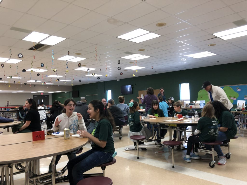 Students sitting and visiting with each other and sitting at round tables in the cafeteria at a Wichita Middle School.