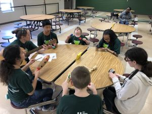 Several Students Wearing Braille Challenge Shirts Sitting Around A Circular Table And Holding Musical Instruments.