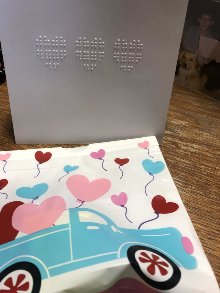A card with three braille hearts and a plastic bag with hearts and a truck image on the front.