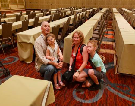 Family sitting near the floor posing for a picture in a large conference room space.