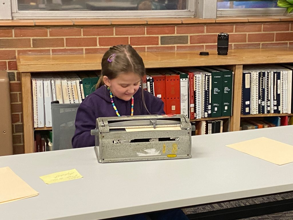 A young child smiling while sitting in front of a braille writer.