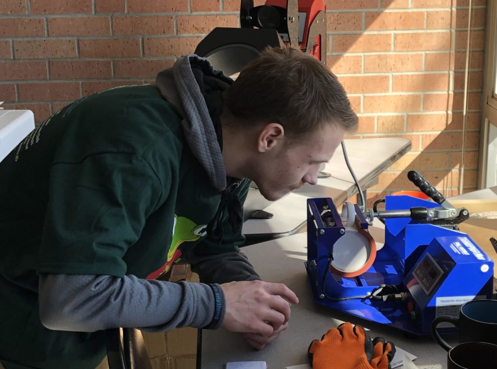 A student bending over a mug label machine.
