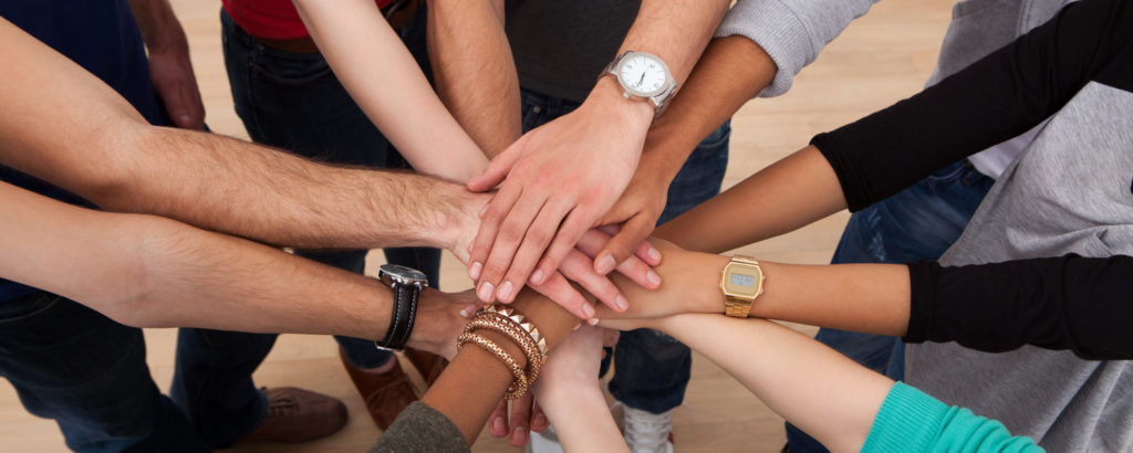 A group of people in a circle showing hands stacked together.