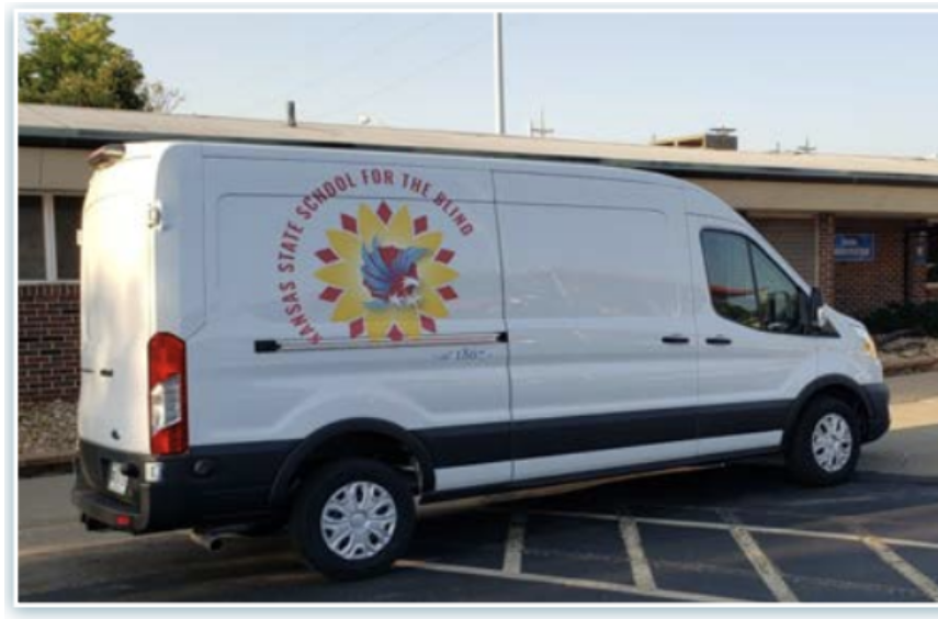 A Large White Van With KSSB's New Logo Is Parked In The Circle Drive, Next To A Display Table Draped With A Cloth.