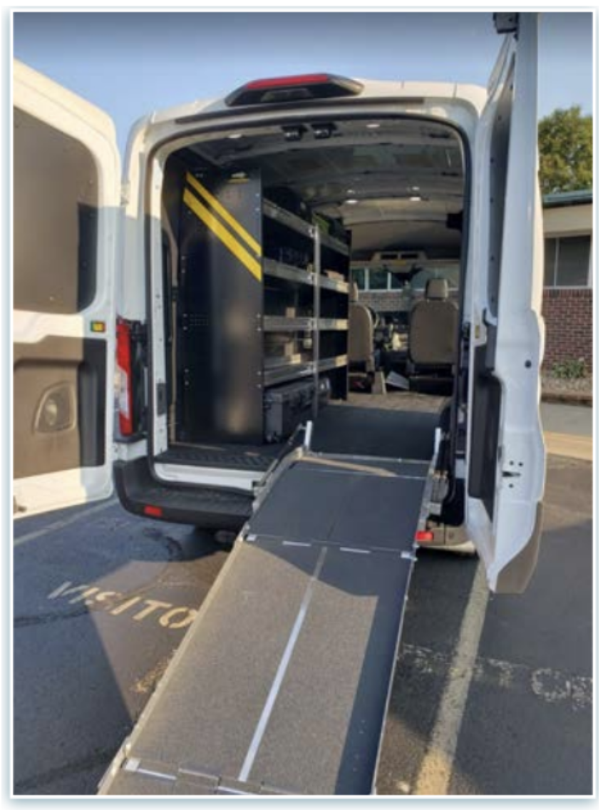 A large ramp leading into the large white van filled with storage shelves and equipment.