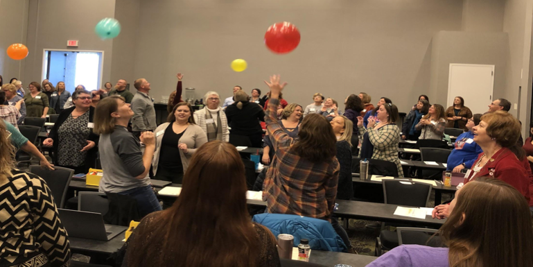 Teachers in a conference room, keeping balloons in the air.