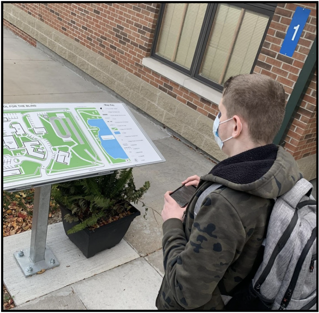 Student, holding a phone and standing in front of a Wayfinding Tactile Map located near entrance to building 1.