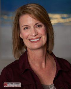 Susan Threinen wearing a dark blue long sleeve collared shirt.