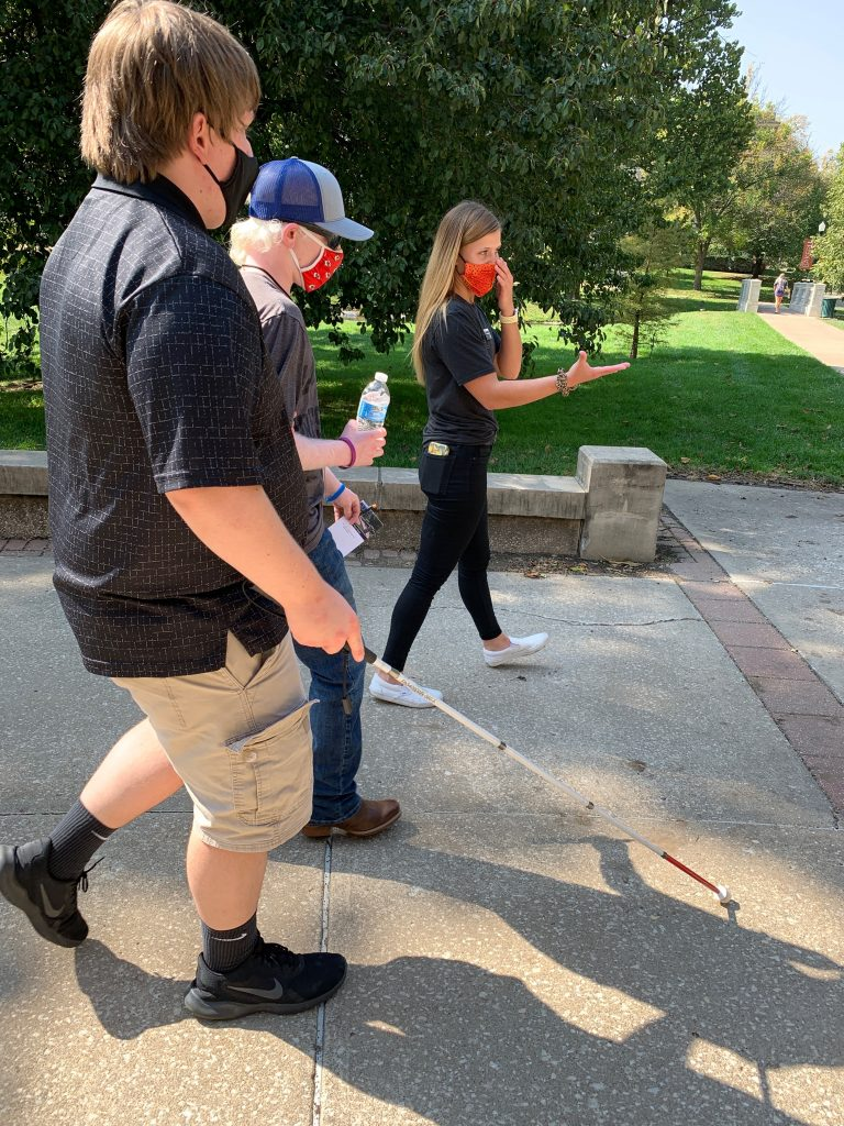 two students walking on a college campus getting a tour from a student at the college