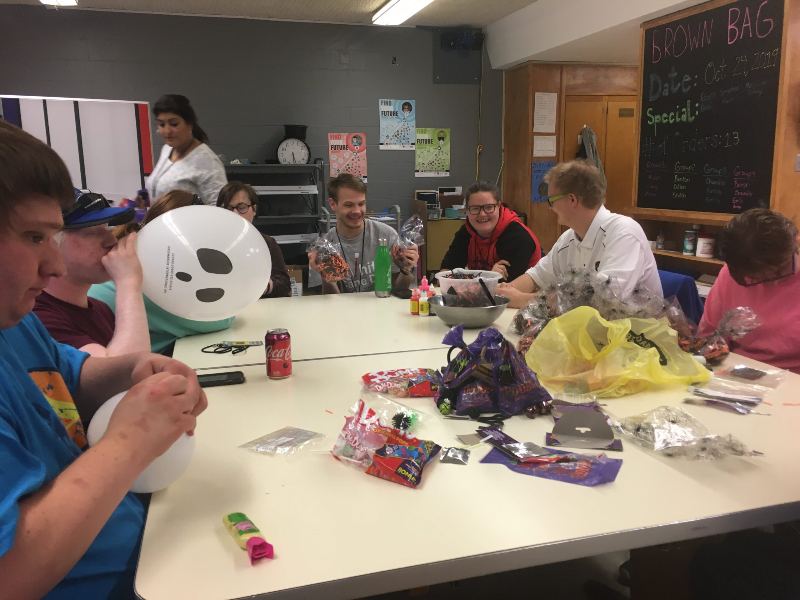 7 students sitting at a table working on a project together. One student is blowing up a balloon with a ghost face on it.