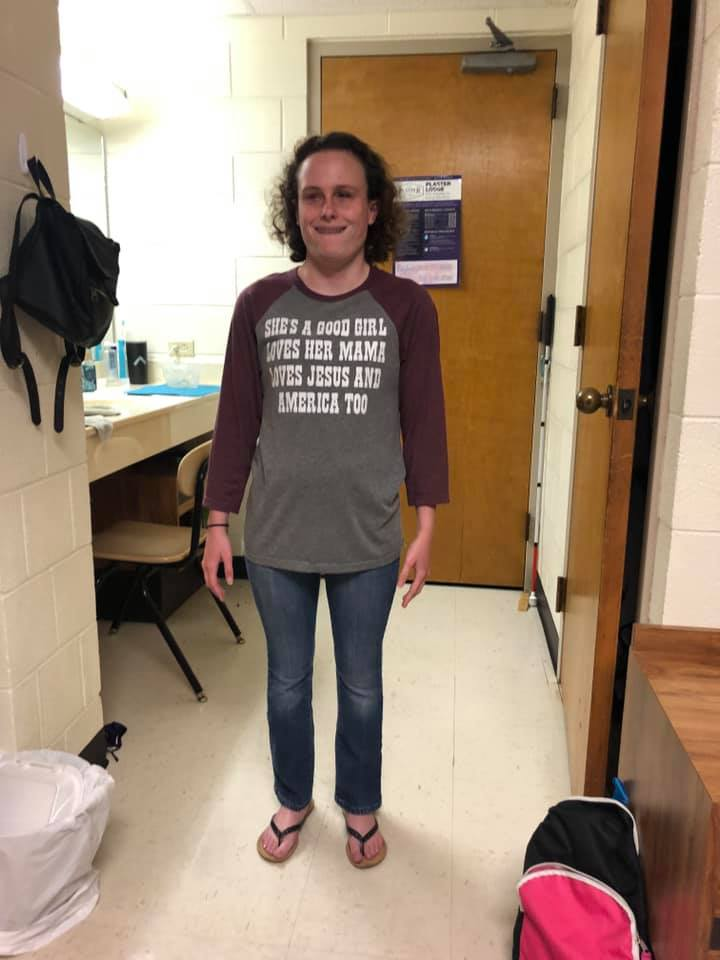 Gracie posing in her dorm room wearing flip flops, jeans and long sleeved t-shirt