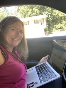 Leah Enright sitting in her parked car with laptop on her lap working