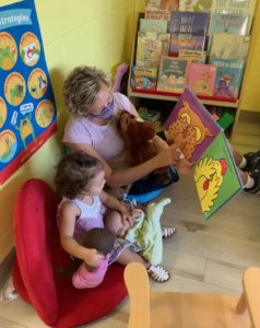 Ms. Jeanne reading a book to a little girl who is sitting in a red chair and holding 2 baby dolls.