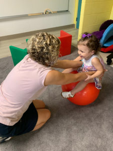 Ms. Jeanne kneeling on the ground holding a little girl on a read stability ball. The girl has a big smile on her face.