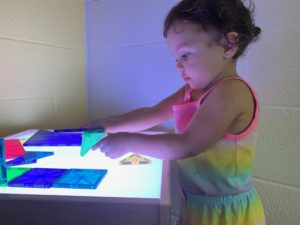 Little girl standing at a light table with different colored shapes on the table.