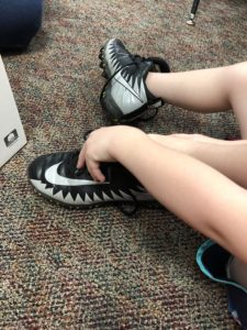 child putting on white and black cleats