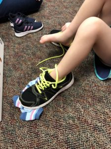 child putting on black tennis shoes with bright yellow laces
