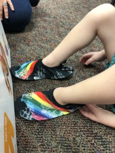 child putting on thin colorful water shoes with a flat bottom