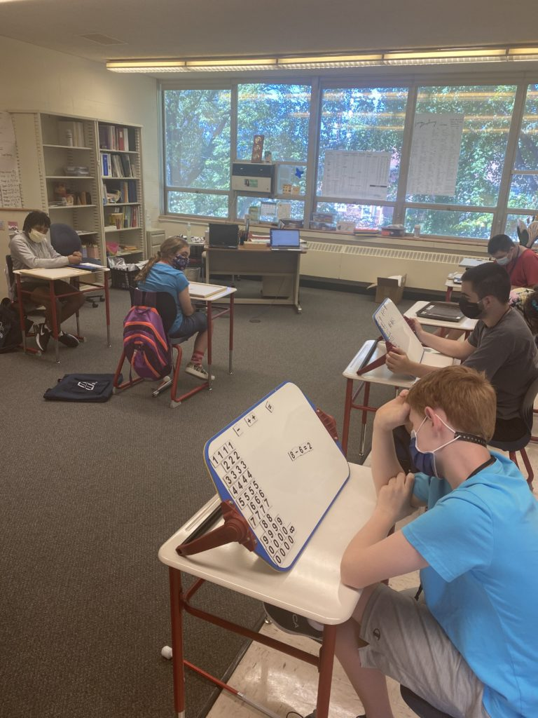 classroom of students sitting at desks with Math Windows and working out problems