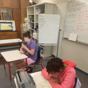 2 Students Sitting At Desks Licking Tootsie Pops