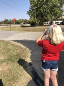 girl with blonde hair, red shirt, and jean shorts using a monocular to view a stop sign in the distance