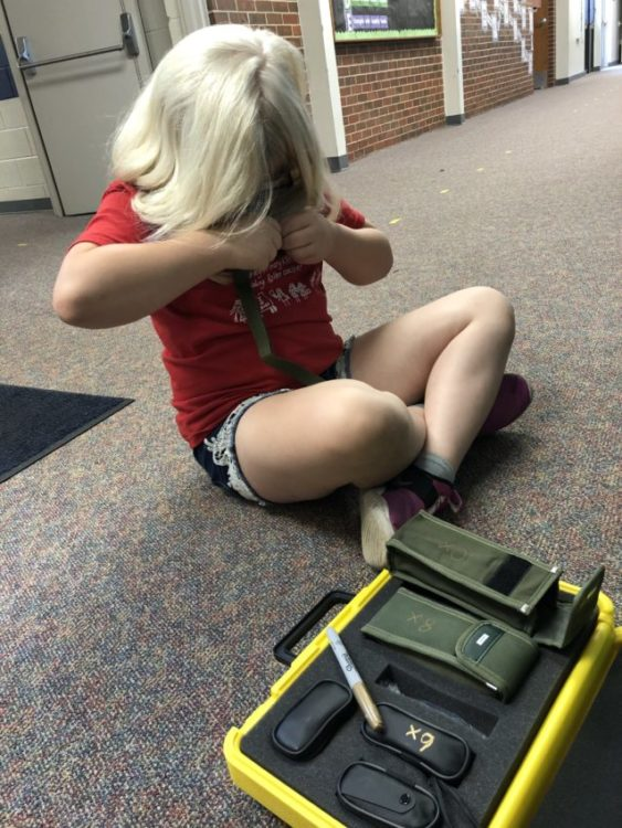 Girl With Blonde Hair And Red Shirt Sitting On The Floor Looking At Different Monculars