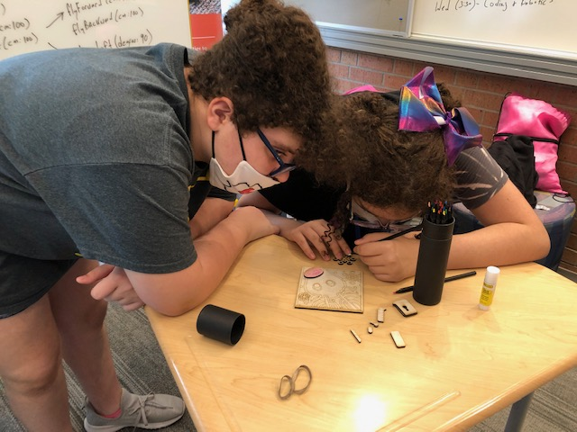 Two Students Leaning Over A Desk Working On A Woodworking Project