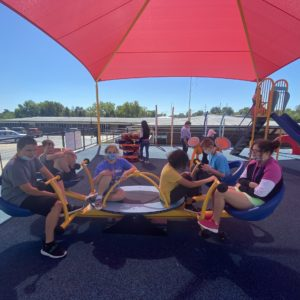 6 Students Balance Themselves On A Teeter Totter