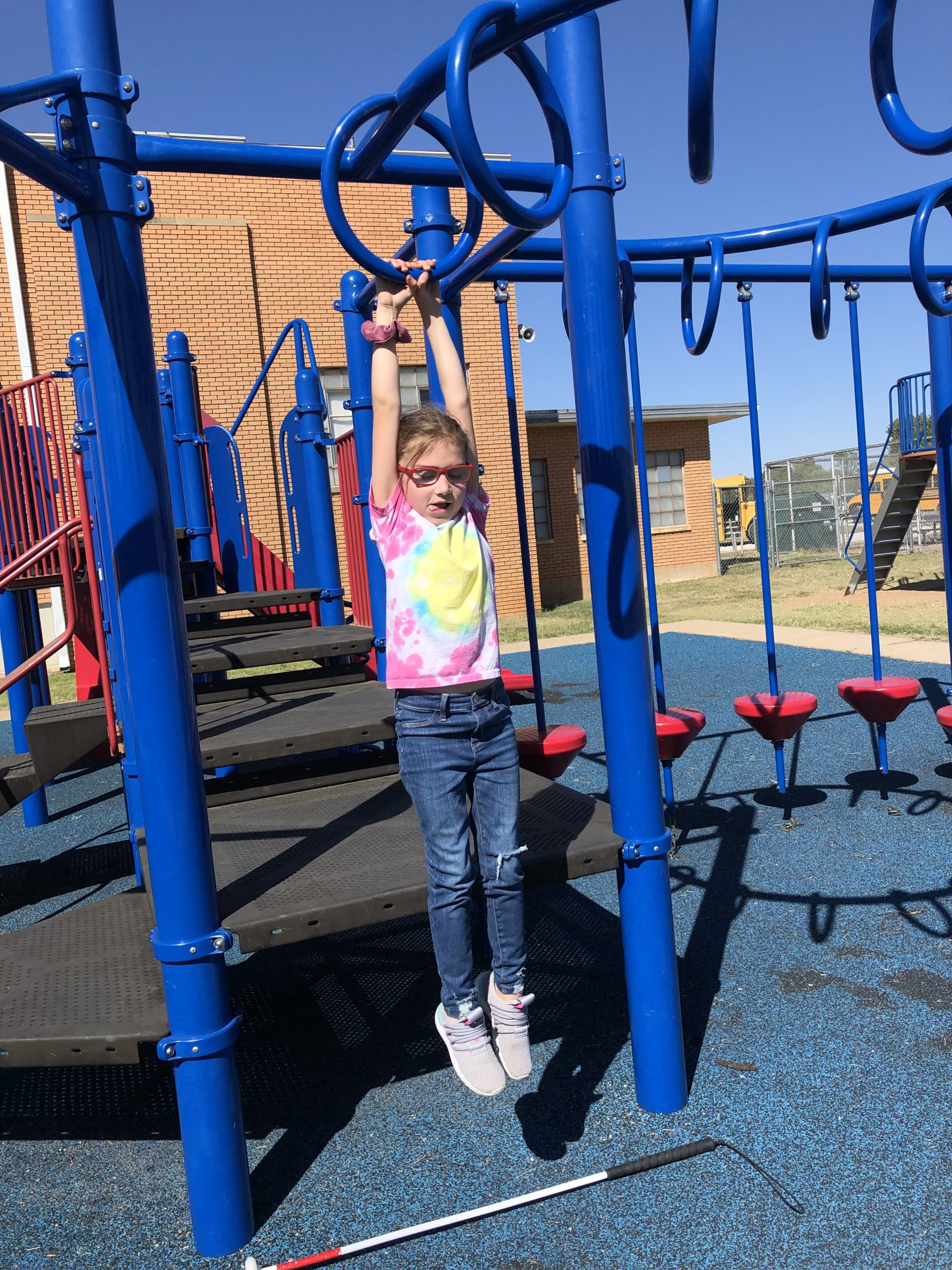 Girl Hanging From Monkey Bars At School Playground